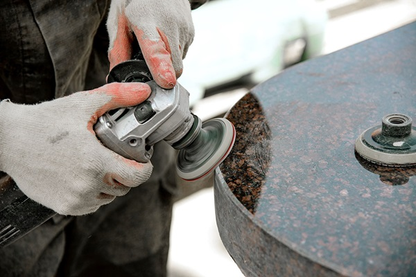 A man works polishing a marble stone with an angle grinder.